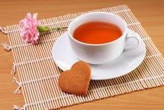 Taza de té con la galleta en forma de corazón Imágenes de archivo libres de regalías