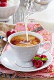 Taza de té con la leche que vierte encima imagenes de archivo