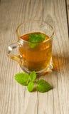 Taza de té con la menta en la tabla de madera Fotos de archivo libres de regalías