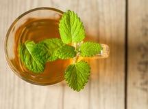 Taza de té con la menta en la tabla de madera Fotos de archivo