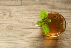 Taza de té con la menta en la tabla de madera Imagen de archivo libre de regalías