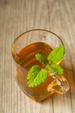 Taza de té con la menta en la tabla de madera Foto de archivo libre de regalías