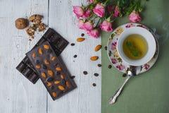 Taza de té con la menta y la barra de chocolate hecha a mano en la tabla vieja Imágenes de archivo libres de regalías