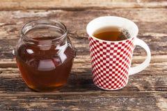 Taza de té con la miel Imagenes de archivo