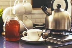 Taza de té con la miel en la tabla Fotos de archivo