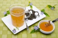 Taza de té con la miel y las flores Fotos de archivo