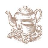 Taza de té con la tetera y verdes Foto de archivo libre de regalías