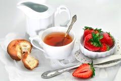 Taza de té con la torta y la fresa Fotos de archivo