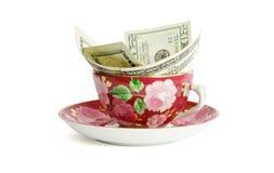 Taza de té con las cuentas de dólar aisladas Imagen de archivo libre de regalías