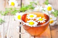 Taza de té con las flores de la manzanilla foto de archivo libre de regalías