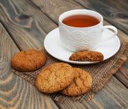 Taza de té con las galletas de harina de avena Fotografía de archivo