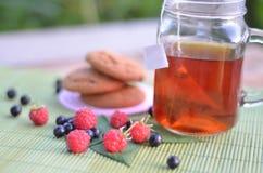 Taza de té con las galletas y las bayas en el primer de la tabla foto de archivo libre de regalías