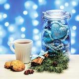 Taza de té con las galletas y el tarro de bola y de gotas de la Navidad Imagen de archivo