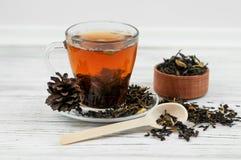 Taza de té con las hojas de té dispersadas Imagenes de archivo
