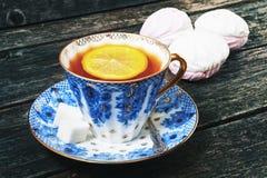 Taza de té con las melcochas del limón, de los terrones del azúcar, blancas y rosadas en el fondo de madera Fotografía de archivo libre de regalías