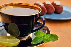 Taza de té con las tortas, la menta y la cal Fotografía de archivo libre de regalías