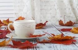 Taza de té con leche inglés en la tabla blanca con las hojas de arce Imagen de archivo libre de regalías