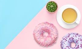 Taza de té con los anillos de espuma en rosa y fondo en colores pastel azul Visi?n superior Concepto dulce puesto plano de la com imagen de archivo libre de regalías