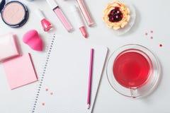 Taza de té con los cosméticos femeninos en la tabla de madera blanca Foto de archivo libre de regalías