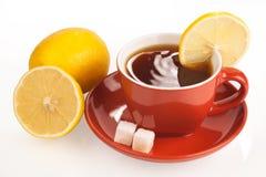 Taza de té con los cubos del limón y del azúcar Foto de archivo libre de regalías