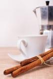 Taza de té con los rollos de canela y el pote del té Imagenes de archivo