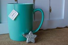Taza de té con un ornamento ideal de la etiqueta y de la estrella Fotografía de archivo libre de regalías