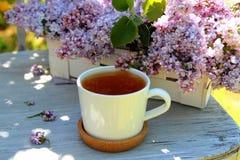 Taza de té con un ramo de lilas Fotos de archivo