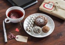 Taza de té con una bolsita de té hecha en casa, dulces - torta, galletas y un caramelo hecho en casa, un regalo hecho en casa del Foto de archivo