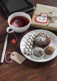 Taza de té con una bolsita de té hecha en casa, dulces - torta, las galletas y un caramelo hecho en casa, regalo hecho en casa de Imagen de archivo libre de regalías