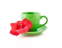 Taza de té con una flor en un fondo blanco Foto de archivo libre de regalías