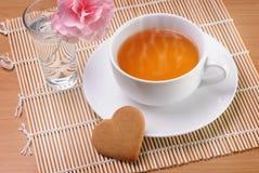 Taza de té con una galleta en forma de corazón Imagen de archivo libre de regalías