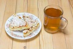 Taza de té con una placa de la torta Fotografía de archivo libre de regalías