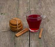 Taza de té, de canela y de lazo rojos de galletas, aún vida Imagenes de archivo