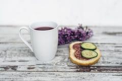 Taza de té de la fruta con el bocadillo del salami y del pepino en la tabla de madera del vintage Fotografía de archivo libre de regalías