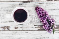 Taza de té de la fruta en la tabla de madera del vintage con la rama de la lila Foto de archivo libre de regalías