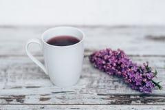 Taza de té de la fruta en la tabla de madera del vintage con la rama de la lila Imagen de archivo libre de regalías
