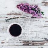 Taza de té de la fruta en la tabla de madera del vintage con la rama de la lila Fotos de archivo libres de regalías