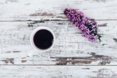 Taza de té de la fruta en la tabla de madera del vintage con la rama de la opinión superior de la lila Fotos de archivo libres de regalías