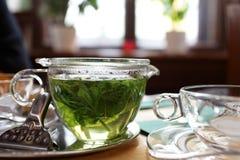 Taza de té de la menta en una tabla imagenes de archivo