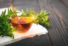 Taza de té de la menta y un manojo de menta en la tabla Foto de archivo libre de regalías