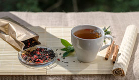 Taza de té de la menta y un manojo de menta en la tabla Fotos de archivo libres de regalías