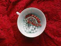 Taza de té de la porcelana con joyería en fondo de encaje rojo Imagen de archivo