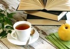taza de té, de libros y de manzana en de madera imágenes de archivo libres de regalías