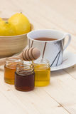 Taza de té, de miel y de limones frescos Foto de archivo libre de regalías
