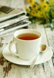 Taza de té, de periódico y de flores en de madera viejo Foto de archivo