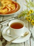 taza de té, de torta y de flores amarillas en de madera viejo Fotos de archivo libres de regalías