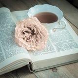 Taza de té, de un libro y de una rosa Imágenes de archivo libres de regalías
