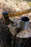Taza de té del hacha y de la taza en tocón fuera de la naturaleza Fotos de archivo libres de regalías