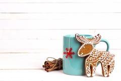 Taza de té del invierno con los ciervos del pan de jengibre y los palillos de canela en w Imágenes de archivo libres de regalías