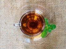 Taza de té en el yute marrón Foto de archivo libre de regalías